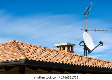 Closeup of a Television Aerial and Satellite Dish on the House Roof on blue sky with clouds