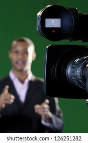 Close-up of a television camera viewfinder and lens with a presenter out of focus in the background. Viewfinder display added in post-production.