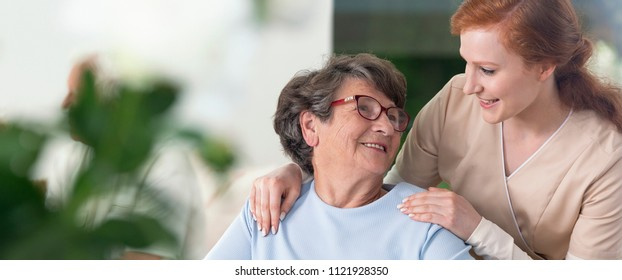 Close-up of a tender caregiver with her hands on the shoulders of a senior woman inside her home. Blurred surrounding. Panorama.