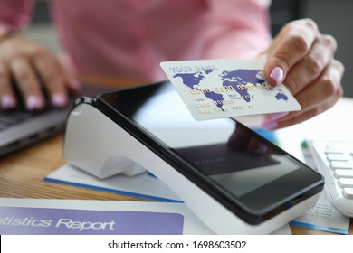 Close-up of tender hand of worker holding credit card. Employee helping pay for service or product using terminal. Cashless payment method. Banking and outpayment concept
