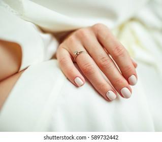 Nahaufnahme eines zärtlichen Ringes auf der Hand der Braut mit weißen Nägeln