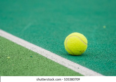 Closeup of tennis ball on court. Tennis ball indoor on tenis court near the white line on synthetic surface