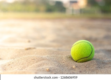 Close-up tennis ball on the sand court and free copy space for your words.