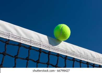 Close-up of a tennis ball touching the net tape with a blue sky background.