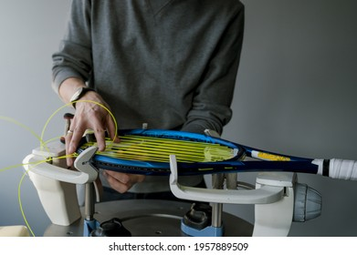 Close-up of tennis racket on electronic stringing machine. Process of replacement synthetic gut string before game. Hands of stringer.
