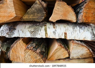 Close-up texture of dry fireplace logs. Wood background. Macro shooting of wood structure. The surface of the chopped campfire logs. Texture of firewood stacked in woodpile.