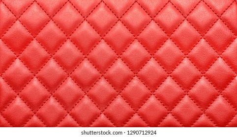 Close-up texture of genuine leather with rhombic stitching. Saturated red color. Luxury background