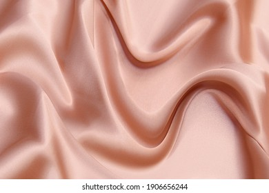 Close-up texture of natural red or pink fabric or cloth in same color. Fabric texture of natural cotton, silk or wool, or linen textile material. Red canvas background.
