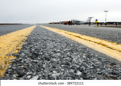 Closeup of the texture of the surface of the asphalt runway of a small airfield. Yellow markings.