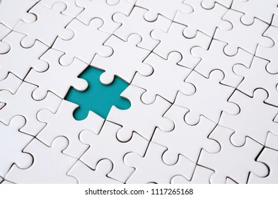 Close-up texture of a white jigsaw puzzle in assembled state with missing elements forming a blue pad for text. Copy space