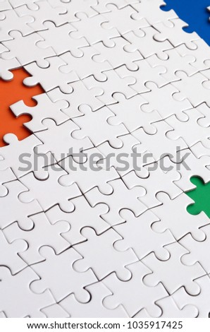 Close-up texture of a white jigsaw puzzle in assembled condition with missing elements, under which surfaces of different colors