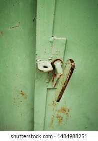 closeup of textured and weathered green painted door with butterfly lock