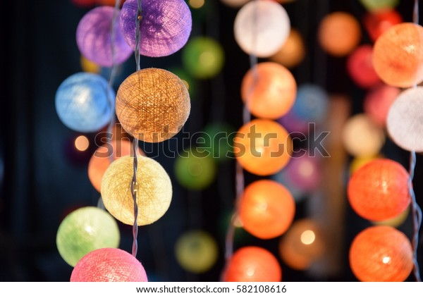 Close-up of a Thai home decoration: ball of yarn lights of several different colors. Feeling of warmth, joy, happiness. Blurry background.