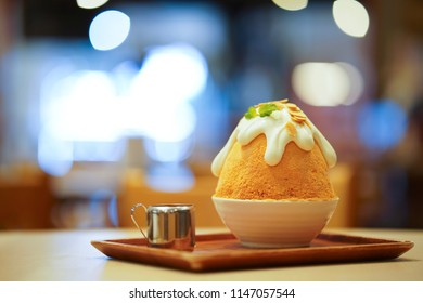 Closeup thai milk tea Bingsu on tray, Bingsu or Bingsoo, Korean shaved ice dessert with sweet toppings and fruit and varieties with ingredients, popular dessert, using as a background or wallpaper