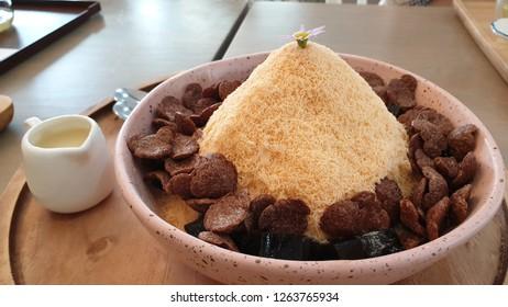 closeup thai tea kakigori with chocolate cornflakes on the wooden cafe