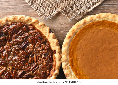 Closeup of a Thanksgiving holiday table with Pumpkin and pecan pies, traditional desserts for the American holiday.