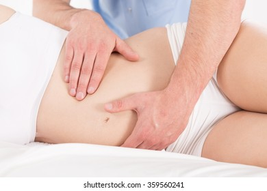 Close-up of therapeutic massage of pregnant woman's belly