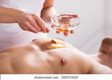Close-up Of A Therapist Applying Wax On Man's Body