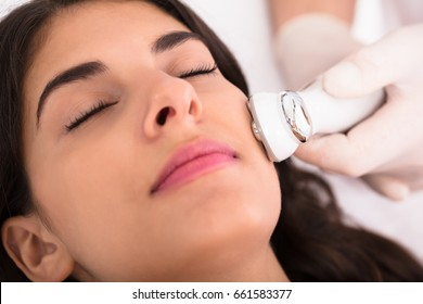 Close-up Of A Therapist Giving Needle Free Mesotherapy Treatment On Women's Face