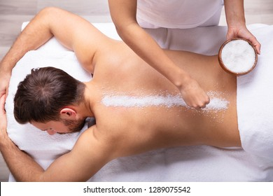 Close-up Of Therapist Hand Applying Salt On Young Man's Back
