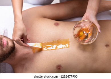 Close-up Of Therapist Hand Applying Wax On Relaxed Young Man's Chest
