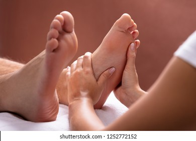 Close-up Of Therapist Hand Giving Foot Massage To Man