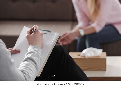 Close-up of therapist hand writing notes during a counseling session with a single woman sitting on a couch in the blurred background.