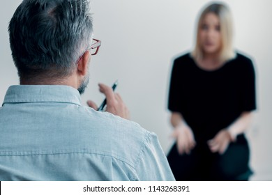 Close-up of a therapist holding a pen talking to his blurred female patient