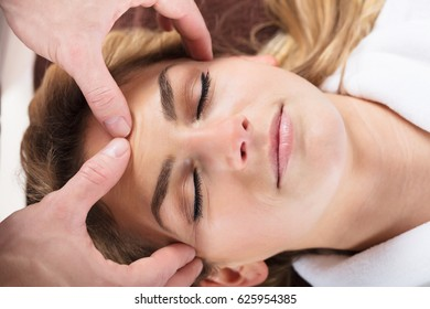 Close-up Of A Therapist Massaging A Beautiful Woman's Forehead At Beauty Spa