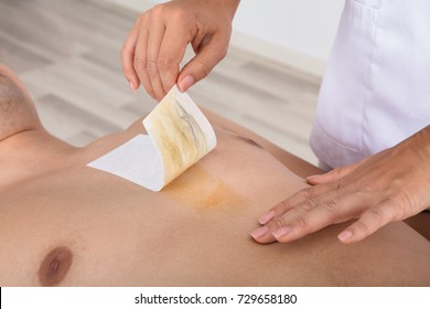 Close-up Of A Therapist Waxing Man's Chest With Wax Strip