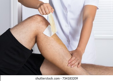 Close-up Of A Therapist Waxing Man's Leg With Wax Strip