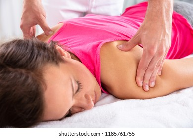 Close-up Of A Therapist's Hand Giving Shoulder Massage To Relaxed Female Patient