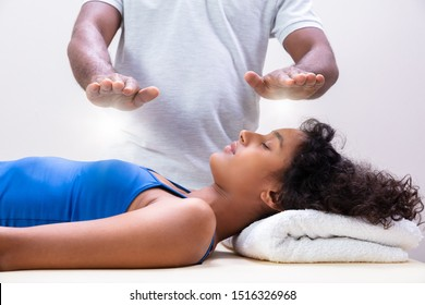 Close-up Of Therapist's Hand Performing Reiki Treatment On Young Woman In Spa