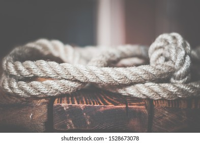 Close-up of a thick hemp rope. Natural rope on an old wooden table. Side view. Soft focus. Eye level shooting.