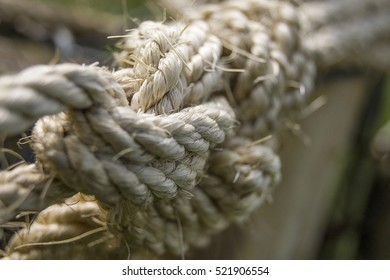 Closeup of a thick, stressed and rough rope tied into a knot.