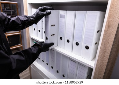 Close-up Of A Thief Stealing Folder From Wooden Shelf