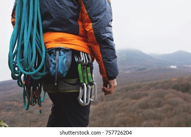 Close-up of a thigh climber with equipment on a belt, stands on a rock