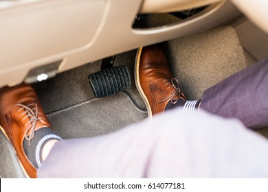 Closeup of a thirties man wearing brown shoes carrying a car accelerator and a brake / car safety system on the feet Accident and brake, danger of auto motor-driven bikes, driving habits
