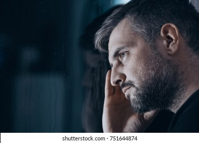 Close-up of thoughtful man with withdrawal symptoms looking through a window