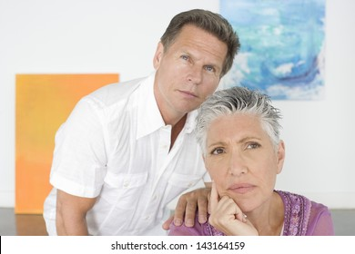 Closeup of thoughtful mature couple in art gallery