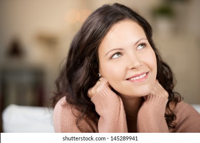Closeup of thoughtful young woman looking up in house
