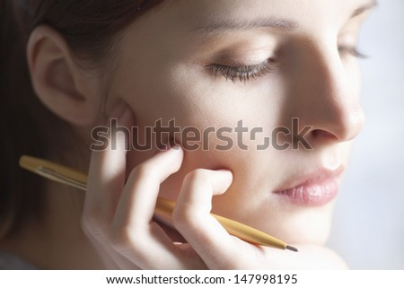 Closeup of thoughtful young woman with pen resting hand on chin