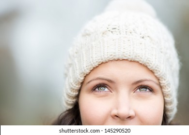 Closeup of thoughtful young woman wearing knit hat while looking up