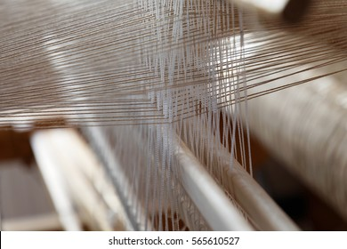 Closeup of threads in a loom used for weaving rag carpets
