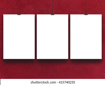 Close-up of three blank frames hanged by clips against red plastered concrete wall background