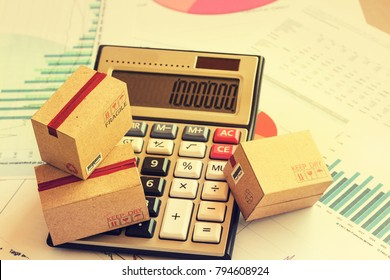 Closeup three cardboard boxes packing the product and calculator on technical chart of financial expansion. Idea of marketing planning and shipping costs, Control financial budget and service charge.