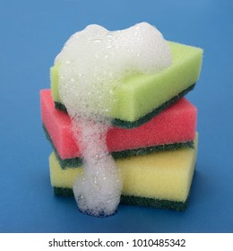 Close-up of three colorful sponges with soap suds on blue background