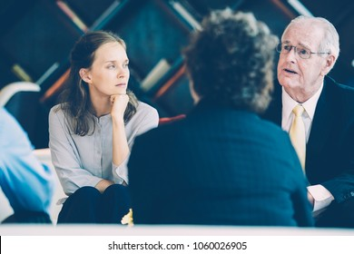 Closeup of three diverse business people listening to senior business leader who is explaining something to them with blurred lounge view in background. Two colleagues are sitting back to camera.