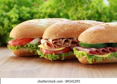 Closeup of three fresh sandwiches with turkey, salami and mozzarella