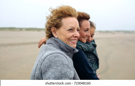 Closeup of three generations female walking on the beach in autumn